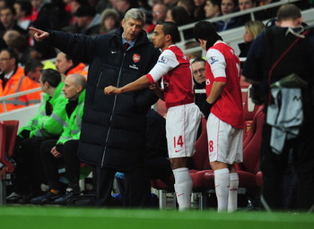 LONDON, ENGLAND - JANUARY 25:  Arsene Wenger manager of Arsenal gives instructions to substitutes Theo Walcott and Samir Nasri during the Carling Cup Semi Final Second Leg match between Arsenal and Ipswich Town at Emirates Stadium on January 25, 2011 in L