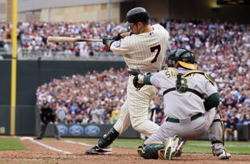 MINNEAPOLIS, MN - APRIL 08:  Joe Mauer #7 of the Minnesota Twins drives in the winning run as Kurt Suzuki #8 of the Oakland Athletics catches during Opening Day on April 8, 2011 at Target Field in Minneapolis, Minnesota. The Minnesota Twins defeated the O