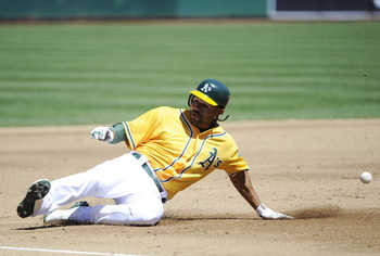 OAKLAND, CA - APRIL 3: Coco Crisp #4 of the Oakland Athletics slides into third-base safe after hitting an rbi triple in the second inning against the Seattle Mariners during a MLB baseball game at the Oakland-Alameda County Coliseum April 3, 2011 in Oakl