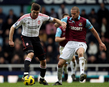 LONDON, ENGLAND - FEBRUARY 27:  Steven Gerrard of Liverpool is challenged by Matthew Upson of West Ham during the Barclays Premier League match between West Ham United and Liverpool at the Boleyn Ground on February 27, 2011 in London, England.  (Photo by