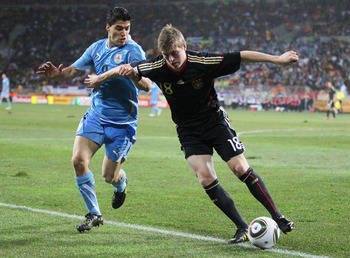 PORT ELIZABETH, SOUTH AFRICA - JULY 10:  Luis Suarez of Uruguay tussles for posession with Toni Kroos of Germany during the 2010 FIFA World Cup South Africa Third Place Play-off match between Uruguay and Germany at The Nelson Mandela Bay Stadium on July 1