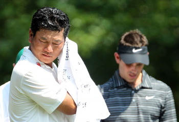 AUGUSTA, GA - APRIL 10:  K.J. Choi of South Korea wipes his face as Charl Schwartzel of South Africa looks on during the final round of the 2011 Masters Tournament at Augusta National Golf Club on April 10, 2011 in Augusta, Georgia.  (Photo by Jamie Squir