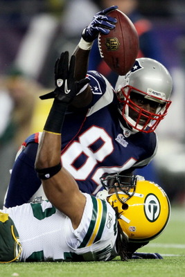 FOXBORO, MA - DECEMBER 19:  Wide receiver Deion Branch #84 of the New England Patriots tries to hold onto the ball during the fourth quarter of the game against the Green Bay Packers at Gillette Stadium on December 19, 2010 in Foxboro, Massachusetts.  (Ph
