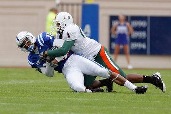 DURHAM, NC - OCTOBER 18:  Eron Riley #15 of the Duke Blue Devils grips the ball as he is tackled by Brandon Harris #1 of the Miami Hurricanes at Wallace Wade Stadium on October 18, 2008 in Durham, North Carolina.  (Photo by Kevin C. Cox/Getty Images)