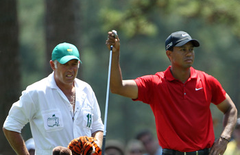 AUGUSTA, GA - APRIL 10:  Tiger Woods pulls a club in the first fairway as his caddie Steve Williams looks on during the final round of the 2011 Masters Tournament at Augusta National Golf Club on April 10, 2011 in Augusta, Georgia.  (Photo by Jamie Squire