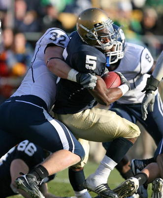 SOUTH BEND, IN - NOVEMBER 21: Armando Allen #5 of the Notre Dame Fighting Irish is stopped by Scott Lutrus #5 of the Univeristy of Connecticut Huskies at Notre Dame Stadium on November 21, 2009 in South Bend, Indiana. (Photo by Jonathan Daniel/Getty Image