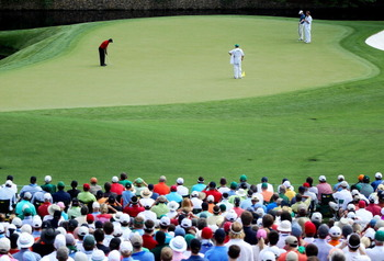 AUGUSTA, GA - APRIL 10:  Tiger Woods hits a putt on the 11th green as Martin Laird of Scotland and their caddies look on during the final round of the 2011 Masters Tournament at Augusta National Golf Club on April 10, 2011 in Augusta, Georgia.  (Photo by