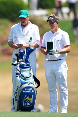 AUGUSTA, GA - APRIL 10:  Luke Donald of England (R) stands alongside his bag with caddie John McLaren on the first hole during the final round of the 2011 Masters Tournament at Augusta National Golf Club on April 10, 2011 in Augusta, Georgia.  (Photo by A