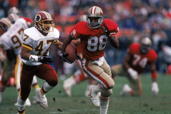 SAN FRANCISCO - JANUARY 12:  Wide receivers Mike Sherrard #88 of the San Francisco 49ers runs away from Washington Redskins cornerback A. J. Johnson #47 during the 1990 NFC Divisional Playoff game at Candlestick Park on January 12, 1991 in San Francisco,