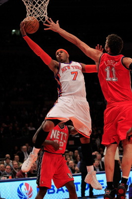 NEW YORK, NY - MARCH 30: Carmelo Anthony #7 of the New York Knicks shoots over Brook Lopez #11 of the New Jersey Nets at Madison Square Garden on March 30, 2011 in New York City. NOTE TO USER: User expressly acknowledges and agrees that, by downloading an