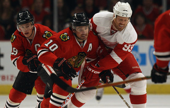 CHICAGO, IL - APRIL 10: Patrick Sharp #10 of the Chicago Blackhawks battles for the puck with Johan Franzen #93 of the Detroit Red Wings as Jonathan Toews #19 trails the play at the United Center on April 10, 2011 in Chicago, Illinois. The Red Wings defea