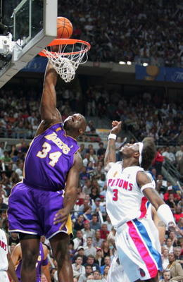 AUBURN HILLS, MI - JUNE 13:  Shaquille O'Neal #34 of the Los Angeles Lakers slam dunks past Ben Wallace #3 of the Detroit Pistons in the first quarter of game four of the 2004 NBA Finals on June 13, 2004 at The Palace of Auburn Hills in Auburn Hills, Mich