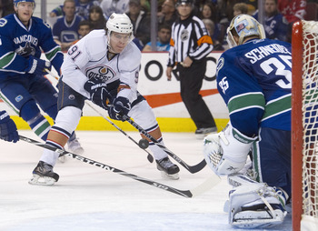 VANCOUVER, CANADA - DECEMBER 26: Magnus Paajarvi #91 of the Edmonton Oilers fires a shot on goalie Cory Schneider #35 of the Vancouver Canucks during the third period in NHL action on December 26, 2010 at Rogers Arena in Vancouver, BC, Canada.  (Photo by