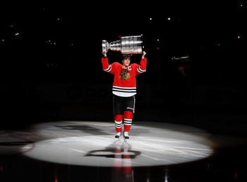 CHICAGO - OCTOBER 09: Jonathan Toews #19 of the Chicago Blackhawks carries the Stanley Cup across the ice in a ceremony before the Blackhawks season home opening game against the Detroit Red Wings at the United Center on October 9, 2010 in Chicago, Illino