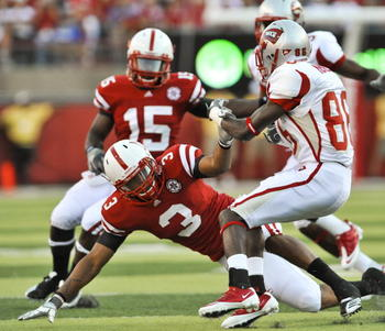 LINCOLN, NE - SEPTEMBER 04:  Willie McNeal #86 of the Western Kentucky Hilltoppers trys to avoid being brought down by Ricky Thenarse #3 of the Nebraska Cornhuskers during first half action of their game at Memorial Stadium on September 4, 2010 in Lincoln