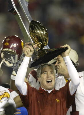 PASADENA, CA - JANUARY 1:  Head coach Pete Carroll of the USC Trojans celebrates with the Tournament of Roses trophy after defeating the Michigan Wolverines in the 2004 Rose Bowl on January 1, 2004 at the Rose Bowl in Pasadena, California. USC defeated Mi