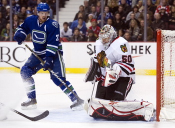 VANCOUVER, CANADA - NOVEMBER 20: Goalie Corey Crawford #50 of the Chicago Blackhawks makes a save while Daniel Sedin #22 looks for a rebound during the second period in NHL action on November 20, 2010 at Rogers Arena in Vancouver, British Columbia, Canada
