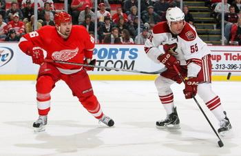 DETROIT - OCTOBER 28:  Ed Jovanovski #55 of the Phoenix Coyotes keeps an eye on the puck as does Tomas Holmstrom #96 of the Detroit Red Wings during their NHL game at Joe Louis Arena on October 28, 2010 in Detroit, Michigan.(Photo By Dave Sandford/Getty I