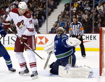 VANCOUVER, CANADA - NOVEMBER 21: Goalie Roberto Luongo #1 of the Vancouver Canucks makes a glove save while Martin Hanzal #11of the Phoenix Coyotes tries to provide a screen during the first period in NHL action on November 21, 2010 at Rogers Arena in Van