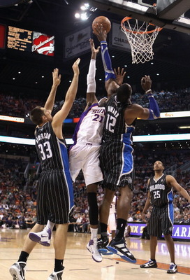 PHOENIX, AZ - MARCH 13:  Hakim Warrick #21 of the Phoenix Suns attempts a shot over Dwight Howard #12 of the Orlando Magic during the NBA game at US Airways Center on March 13, 2011 in Phoenix, Arizona. The Magic defeated the Suns 111-88.  NOTE TO USER: U