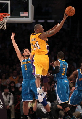 LOS ANGELES, CA - JANUARY 07:  Kobe Bryant #24 of the Los Angeles Lakers dishes of the ball in front of Marco Belinelli #8 of the New Orleans Hornets at Staples Center on January 7, 2011 in Los Angeles, California.  The Lakers won 101-97.  NOTE TO USER: U
