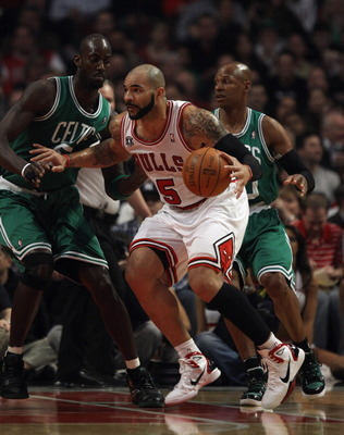 CHICAGO, IL - APRIL 07: Carlos Boozer #5 of the Chicago Bulls moves against Kevin Garnett #5 (L) and Ray Allen #20 of the Boston Celtics at United Center on April 7, 2011 in Chicago, Illinois. The Bulls defeated the Celtics 97-81. NOTE TO USER: User expre