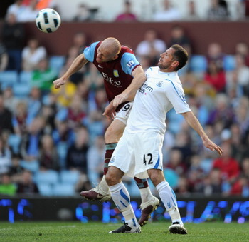 BIRMINGHAM, ENGLAND - APRIL 10:  James Collins of Aston Villa and Shefki Kuqi of Newcastle United battle for the ball during the Barclays Premier League match between Aston Villa and Newcastle United at Villa Park on April 10, 2011 Birmingham, England.  (
