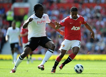 MANCHESTER, ENGLAND - APRIL 09:  Patrice Evra of Manchester United is closed down by Dickson Etuhu of Fulham during the Barclays Premier League match between Manchester United and Fulham at Old Trafford on April 9, 2011 in Manchester, England.  (Photo by
