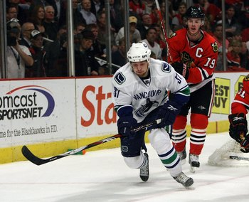 CHICAGO - MAY 11:  Rick Rypien #37 of the Vancouver Canucks attempts to control the puck against Brian Campbell #51 and Jonathan Toews #19 of the Chicago Blackhawks during Game Six of the Western Conference Semifinal Round of the 2009 Stanley Cup Playoffs
