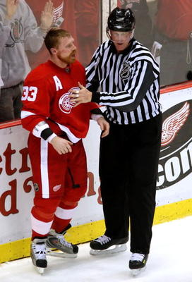 DETROIT - MAY 10:  Kris Draper #33 of the Detroit Red Wings is talked to by linesman Jean Morin after a scrum in game two of the Western Conference Finals of the 2008 NHL Stanley Cup Playoffs against the Dallas Stars at Joe Louis Arena on May 10, 2008 in