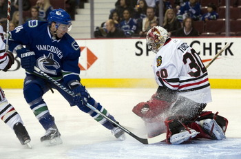 VANCOUVER, CANADA - FEBRUARY 4: Alexandre Burrows #14 of the Vancouver Canucks fails to get a handle on the loose puck after goalie Marty Turco #30 of the Chicago Blackhawks made a pad save during the second period in NHL action on February 04, 2011 at Ro