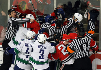 CHICAGO - MAY 05:  Officials attempt to seperate players from the Chicago Blackhawks and the Vancouver Canucks as they fight along the boards during the first period of Game Three of the Western Conference Semifinal Round of the 2009 Stanley Cup Playoffs