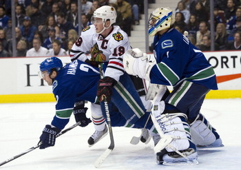 VANCOUVER, CANADA - FEBRUARY 4: Jonathan Toews #19 of the Chicago Blackhawks battles with Dan Hamhuis #2 of the Vancouver Canucks for position in front of goalie Roberto Luongo #1 during the first period in NHL action on February 04, 2011 at Rogers Arena
