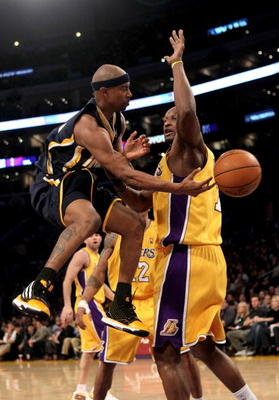 LOS ANGELES, CA - MARCH 02:  T.J. Ford #5 of the Indiana Pacers passes around Lamar Odom #7 of the Los Angeles Lakers on March 2, 2010 at Staples Center in Los Angeles, California. The Lakers won 122-99.  NOTE TO USER: User expressly acknowledges and agre