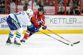 WASHINGTON - JANUARY 14:  Kevin Bieksa #3 of the Vancouver Canucks battles for the puck with Matt Hendricks #26 of the Washington Capitals at the Verizon Center on January 14, 2011 in Washington, DC.  (Photo by Greg Fiume/Getty Images)