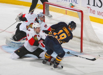 BUFFALO, NY - FEBRUARY 25: Chris Phillips #4 of the Ottawa Senators stops a shot with the shaft of his stick on Tim Connolly #19 of the Buffalo Sabres at HSBC Arena on February 25, 2011 in Buffalo, New York. Buffalo won 4-2.  (Photo by Rick Stewart/Getty