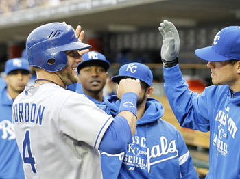 DETROIT - APRIL 09: Alex Gordon #4 of the Kansas City Royals is congratulated by his teammates after scoring in the ninth inning on a sacrifice fly off the bat of Jeff Francoeur (not in photo) during the game against the Detroit Tigers at Comerica Park on