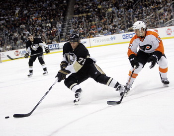 PITTSBURGH, PA - MARCH 29:  Alexei Kovalev #72 of the Pittsburgh Penguins handles the puck in front of Daniel Carcillo #13 of the Philadelphia Flyers at Consol Energy Center on March 29, 2011 in Pittsburgh, Pennsylvania.  (Photo by Justin K. Aller/Getty I