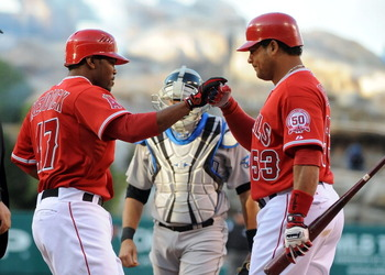 ANAHEIM, CA - APRIL 09:  (L-R)Howie Kendrick #47 celebrates with teammate Bobby Abreu #53 of the Los Angeles Angels of Anaheim after scoring in the first inning against the Toronto Blue Jays at Angel Stadium of Anaheim on April 9, 2011 in Anaheim, Califor