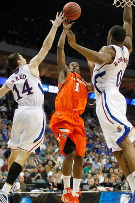 TULSA, OK - MARCH 20:  D.J. Richardson #1 of the Illinois Fighting Illini goes up for a shot against Tyrel Reed #14 and Thomas Robinson #0 of the Kansas Jayhawks during the third round of the 2011 NCAA men's basketball tournament at BOK Center on March 20