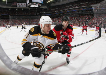 NEWARK, NJ - APRIL 10: Rod Pelley #10 of the New Jersey Devils checks Gregory Campbell #11 of the Boston Bruins at the Prudential Center on April 10, 2011 in Newark, New Jersey.  The Devils defeated the Bruins 3-2. (Photo by Bruce Bennett/Getty Images)