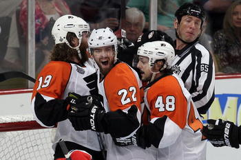 CHICAGO - MAY 29:  (C) Ville Leino #22 of the Philadelphia Flyers celebrates with teammates Scott Hartnell #19 and Danny Briere #48 after scoring a first period goal against the Chicago Blackhawks in Game One of the 2010 NHL Stanley Cup Final at the Unite