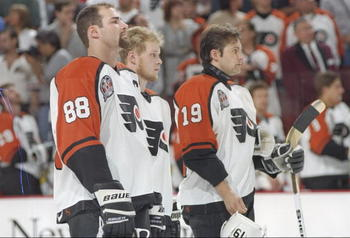 31 May 1997:  Philadelphia Flyers center Eric Lindros (left) and rightwinger Mikael Renberg (right) flank an unidentified teammate during Game 1 of the Stanley Cup Finals against the Detroit Red Wings at the CoreStates Center in Philadelphia, Pennsylvania