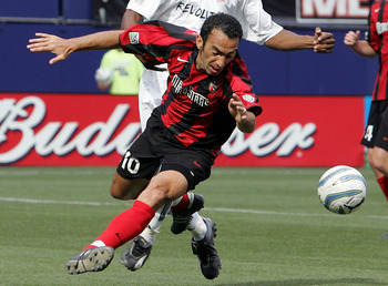 EAST RUTHERFORD, NJ - MAY 21:  Youri Djorkaeff #10 of the Metro Stars is defended by Avery John #4 of the New England Revolution as he tries to play the ball during their Major League Soccer match on May 21, 2005 at Giants Stadium in East Rutherford, New