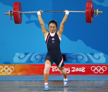 BEIJING - AUGUST 10:  Prapawadee Jaroenrattanatarakoon of Thailand successfully completes a lift to break the Olympic record to win the gold medal in the women's 53kg group A weightlifting event held at the Beijing University of Aeronautics & Astronautics