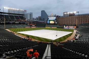 BALTIMORE, MD - APRIL 08:  A tarp covers the field before the game between the Baltimore Orioles and the Texas Rangers at Oriole Park at Camden Yards on April 8, 2011 in Baltimore, Maryland. The start of the game has been delayed due to rain. (Photo by Gr