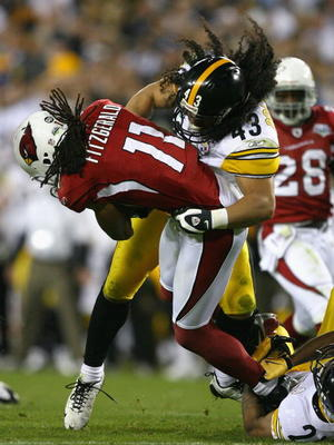 TAMPA, FL - FEBRUARY 01:  Larry Fitzgerald #11 of the Arizona Cardinals gets tackled by Troy Polamalu #43 of the Pittsburgh Steelers in the fourth quarter during Super Bowl XLIII on February 1, 2009 at Raymond James Stadium in Tampa, Florida.  (Photo by A