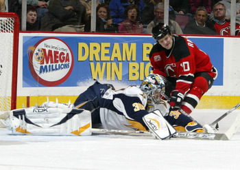 EAST RUTHERFORD, NJ - FEBRUARY 03: Ryan Miller #30 of the Buffalo Sabres makes a diving save as Erik Rasmussen #10 goes for a rebound during their game at the Continental Airlines Arena on February 3, 2007 in East Rutherford, New Jersey.  (Photo by Andy M