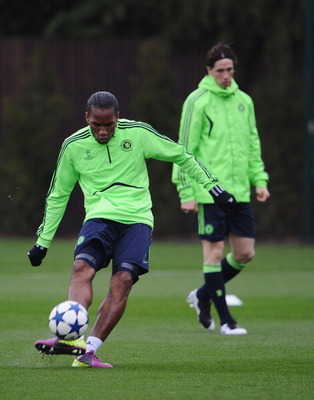 COBHAM, ENGLAND - APRIL 05:  Didier Drogba of Chelsea shoots as team mate Fernando Torres looks on during a Chelsea training session ahead of their UEFA Champions League Quarter-final first leg match against Manchester United, at the Chelsea Football Club