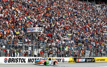 BRISTOL, TN - MARCH 20: Kyle Busch, driver of the #18 M&M's Toyota, takes the checkered flag to win the NASCAR Sprint Cup Series Jeff Byrd 500 Presented By Food City at Bristol Motor Speedway on March 20, 2011 in Bristol, Tennessee.  (Photo by Geoff Burke